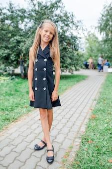 Счастливая школьница позирует в школе ourdoors
