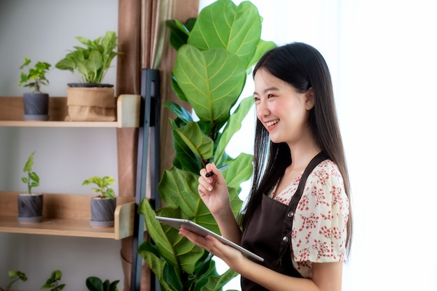 アジアの女性ousコンピュータータブレット彼女のホームオフィスで彼女の顧客からオンライン注文を受け取る、この画像はsme、ビジネス、植物、仕事、およびスタートアップのコンセプトに使用できます。