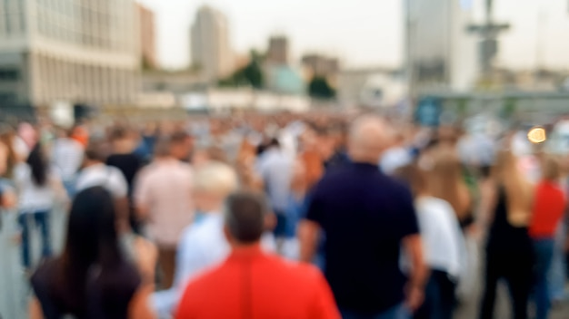Out of focus image of big crowd of people walking on the city street