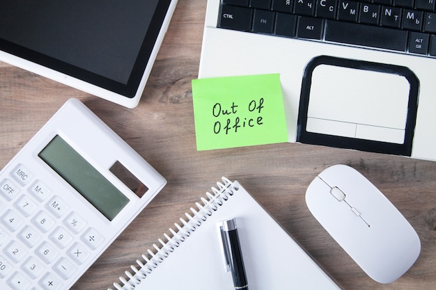 Out of office message on sticky note with computer.