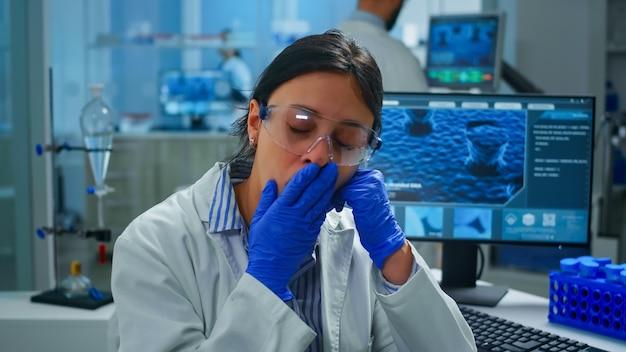 カメラに疲れてあくびをしている近代的な設備の整った研究室に座っている発生化学者。科学研究、ワクチン開発のためのハイテクおよび化学ツールを使用してウイルスの進化を調べる科学者