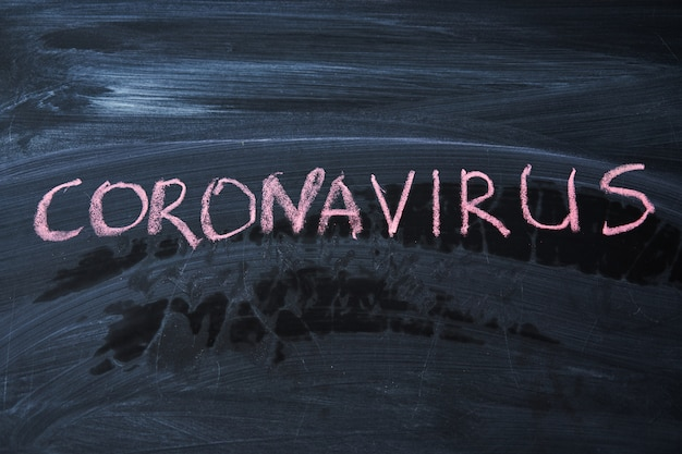 Outbreak warning. written white chalk on blackboard in connection with epidemic of coronavirus worldwide. covid 19 pandemic text on black background with free space.