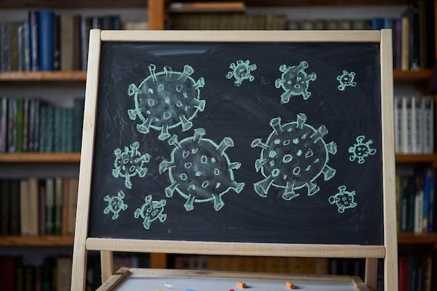 발발 경고. 전세계 코로나 바이러스 전염병과 관련하여 칠판에 흰색 분필을 작성합니다. 공간이 검은 배경에 covid 19 유행성 텍스트. 그려진 바이러스 박테리아