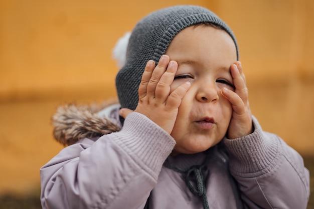 女の赤ちゃんは彼女の頭に手で驚いた。 outddors冬の日。ワオ