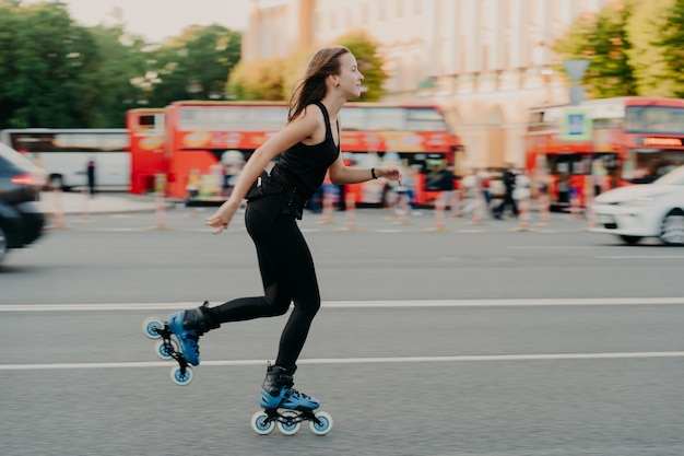 Outdoor activities for being healthy and fit. european woman in good physical shape rides on rollers rolleblades on inline skates dressed in active wear has active rest. sporty lifestyle concept