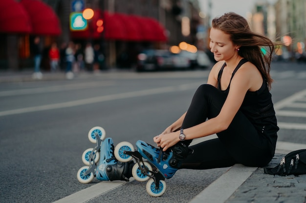 Outdoor activities fit lifestyle. sideways shot of active woman sits on road adjustes rollerblades prepares for skating puts on inline skates has hair floating on wind enjoys weekend favorite hobby