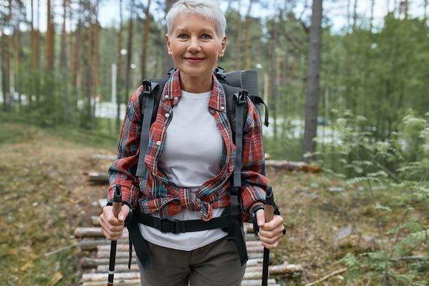 アウトドアアクティビティ、人と休暇のコンセプト。ノルディックウォーキング、有酸素運動、自然を楽しむためにポールを使用して森でハイキングするアクティブウェアの中年女性の魅力的な短い髪