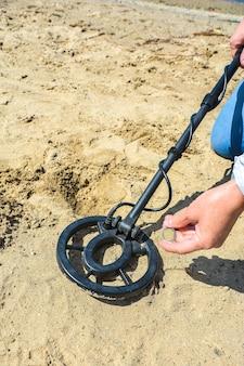 Активный отдых на свежем воздухе мужчина обнаружил монету на песке с помощью металлоискателя.