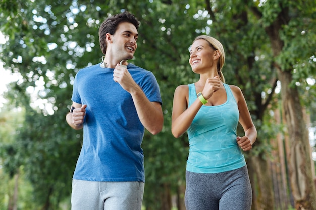 Outdoor activity. nice healthy couple smiling while jogging together in the wood