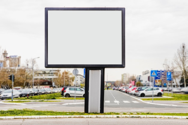An outdoor advertising billboard in front of parking lot
