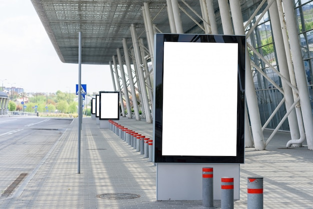 Outdoor advertising poster next to the columns of a modern building.