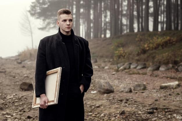 Уличный художник на пляже у моря и леса, молодой мужчина-художник гуляет осенью у моря