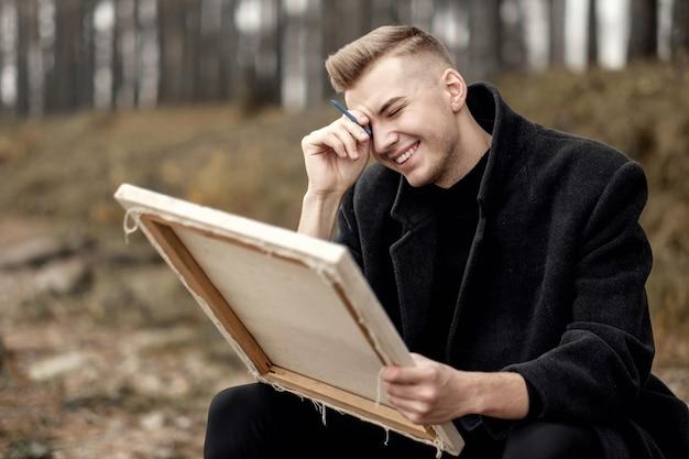Художник на природе, молодой человек рисует на природе, фотомодель в пальто