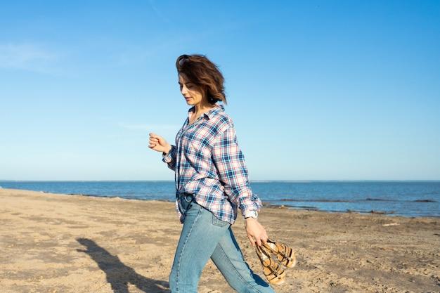 シャツとジーンズのビーチで若い美しい暗い髪の女性の屋外の大気のライフスタイル写真
