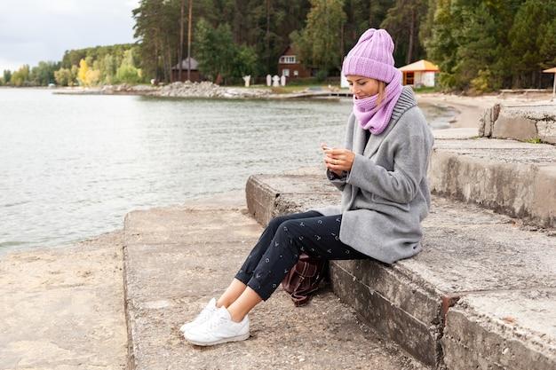 화창한 가을날 바다 옆 부두에 앉아 회색 코트와 검은색 바지를 입고 뜨개질 모자를 쓴 젊고 아름다운 검은 머리 여성의 야외 분위기 있는 라이프스타일 사진