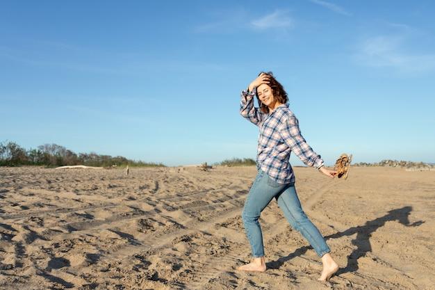 シャツとジーンズのビーチで若い美しいdarkhaired女性の屋外の大気のライフスタイル写真