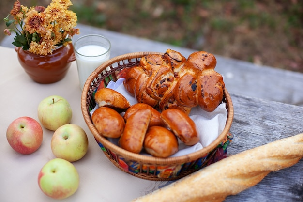 Outdoor autumn picnic with bread, a buns, applesand bouquet of flowers on wooden table