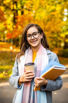 Outdoor autumn portrait happy smiling teenage girl with copybooks