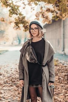 유럽 도시의 거리에서 걷는 젊은 여자의 야외 가을 초상화.