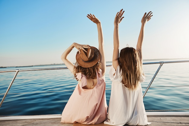 Outdoor back view of two young female on luxury vacation, waving at seaside while sitting on yacht.