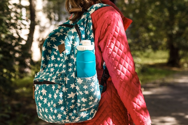 Outdoor backpack with water bottle on the back of a girl on green background nature