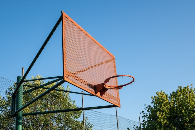 Outdoor basketball hoop with blue sky and trees