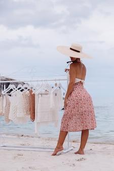 Открытый пляжный магазин вязаной одежды выбор женщины, что купить на напольной вешалке концепция летнего трикотажа