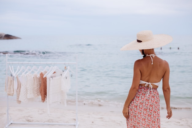 Negozio all'aperto sulla spiaggia per la scelta di vestiti lavorati a maglia donna cosa comprare da appendiabiti concetto di abbigliamento lavorato a maglia estivo