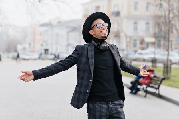 공원에서 주말을 즐기는 안경에 야외 흑인 남자. 도시에서 하루를 보내고 행복을 표현하는 꿈꾸는 아프리카 남자를 웃고.