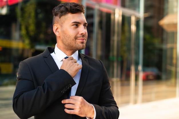 Uomo d'affari all'aperto che organizza la sua cravatta