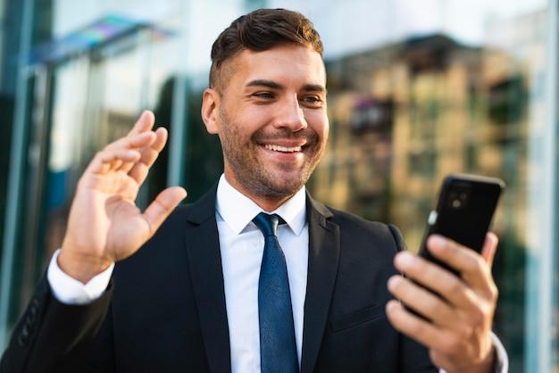 Uomo d'affari all'aperto che tiene telefono e sorrisi