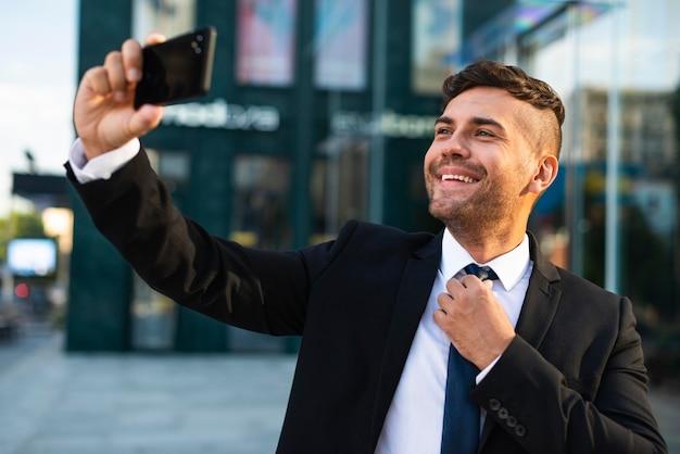 Uomo d'affari all'aperto che cattura una foto di auto