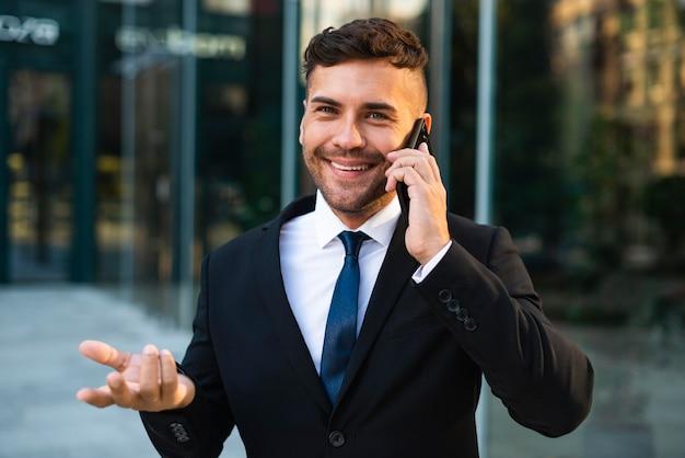 Uomo d'affari all'aperto parlando al telefono con un cliente