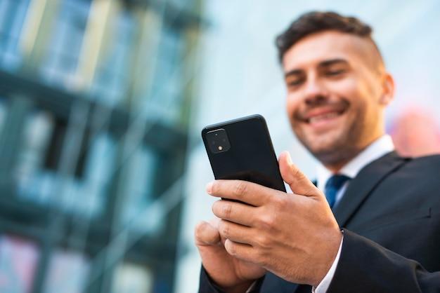 Открытый бизнесмен, используя телефон низкий вид