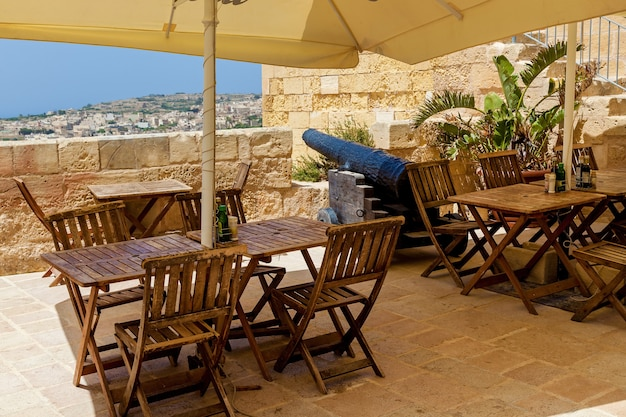 An outdoor cafe terrace with tables and chairs with a view of a coastal city on a sunny day.