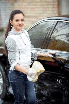 黄色いスポンジで屋外の洗車。