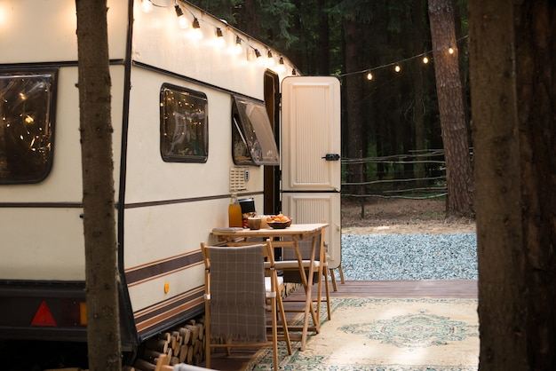 Outdoor caravan trailer parked in camping decorated with light garlands