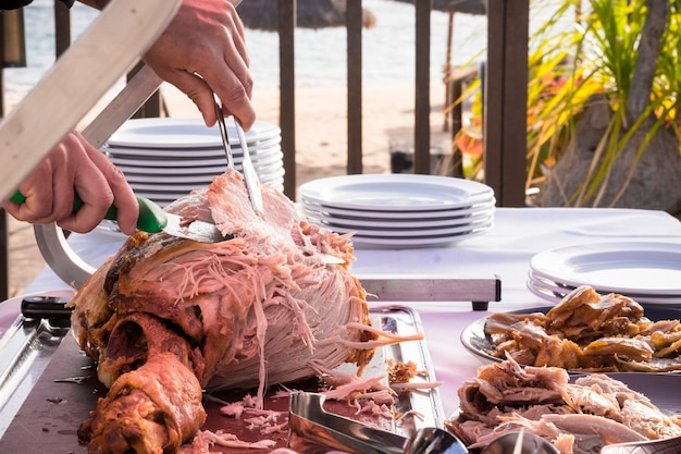 레스토랑이나 케이터링 개념과 요리사 남자가 맛있는 좋은 큰 칠면조를 자르고 제공하는 야외 축하