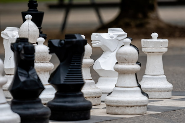 Outdoor chess board with big plastic pieces. outdoor giant chess in public area zone, close up big pieces of street chess in the park