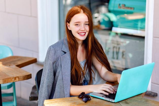 Открытый городской моды портрет молодой бизнес-леди, работающей в кафе на террасе в солнечный день, повседневной стильной одежды, деталей мяты, с использованием ее ноутбука, перерыва в кафе, бизнес-концепции.