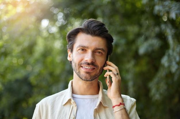 Primo piano all'aperto di affascinante giovane uomo dai capelli scuri con la barba che parla sul suo telefono cellulare mentre si cammina lungo il giardino verde in giornata di sole