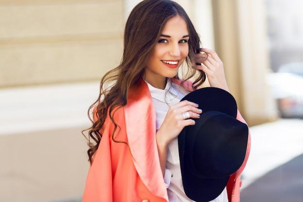 屋外は黒い帽子、ピンクのスーツ、古い通りでポーズをとって白いブラウスでセクシーなスタイリッシュなカジュアルな女性のファッションポートレートを閉じます。春、秋の晴れた日。ウェーブのかかった髪型。