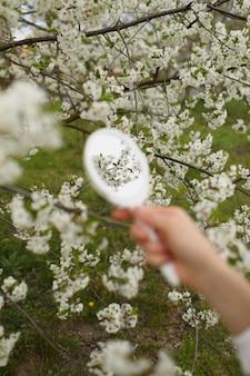 春の日に咲く庭で小さなレトロな鏡を持っている若い女性の手の屋外のクローズアップ。