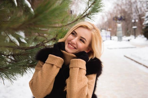 Открытый крупным планом фото молодой красивой счастливой улыбающейся девушки, идущей по улице зимой