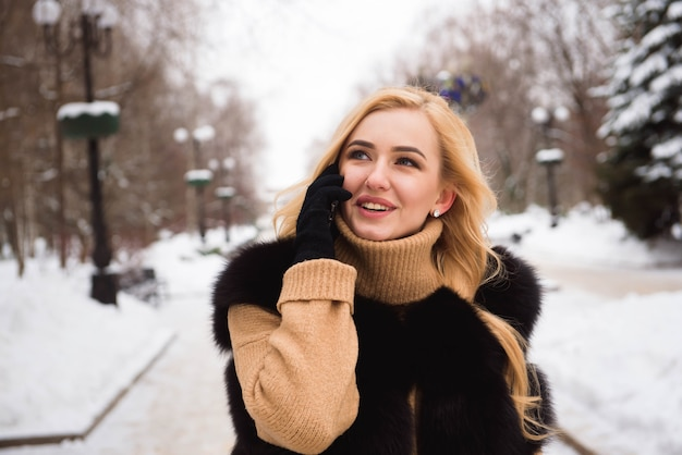 冬の街を歩いている若い美しい幸せな笑顔の女の子の屋外クローズアップ写真