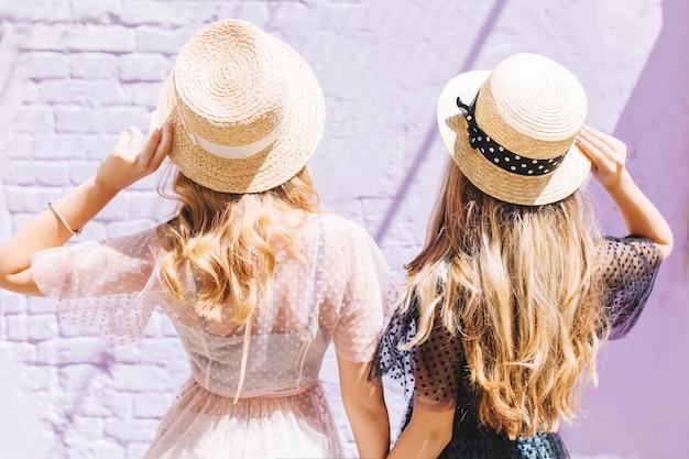 晴れた朝に一緒に時間を過ごす金髪の巻き毛の姉妹の後ろからの屋外のクローズアップの肖像画