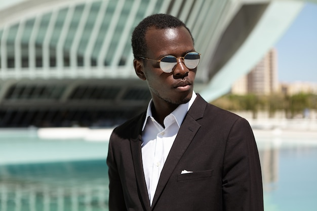 Outdoor close up portrait of handsome confident young afro american dressed formally standing on street in urban setting with modern office building