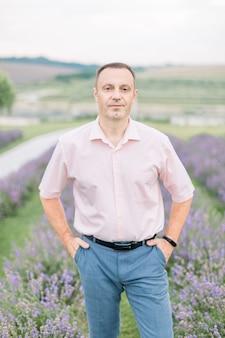 エレガントな服を着て、ラベンダー畑を歩いている50歳の男性の屋外クローズアップの肖像画
