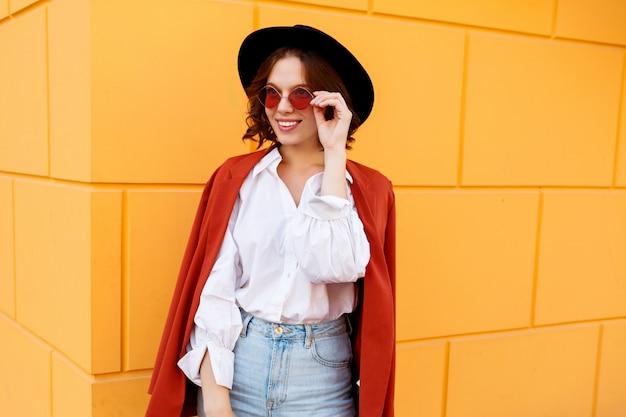 黄色の壁を越えてポーズ至福のブルネットの短い髪の女性の肖像画間近で屋外。トレンディな帽子、ピンクのメガネ、白いブラウス、ジーンズ。