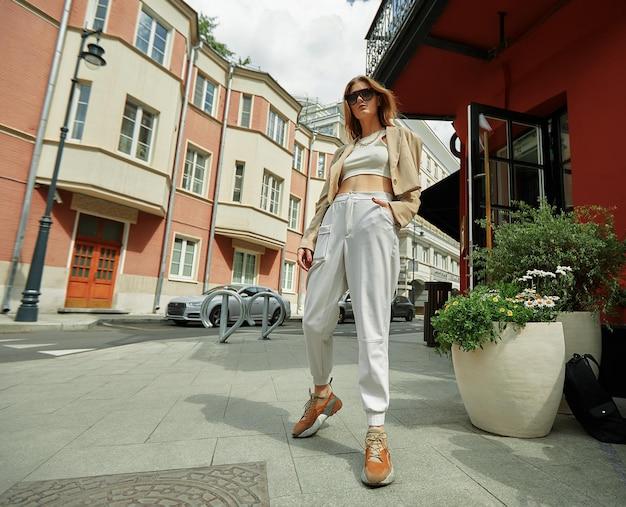 거리에서 포즈를 취하는 젊은 아름 다운 유행 소녀의 야외 초상화를 닫습니다. 세련된 선글라스와 밝은 색상의 옷을 입은 모델. 도시 생활입니다. 여성 패션 개념입니다.